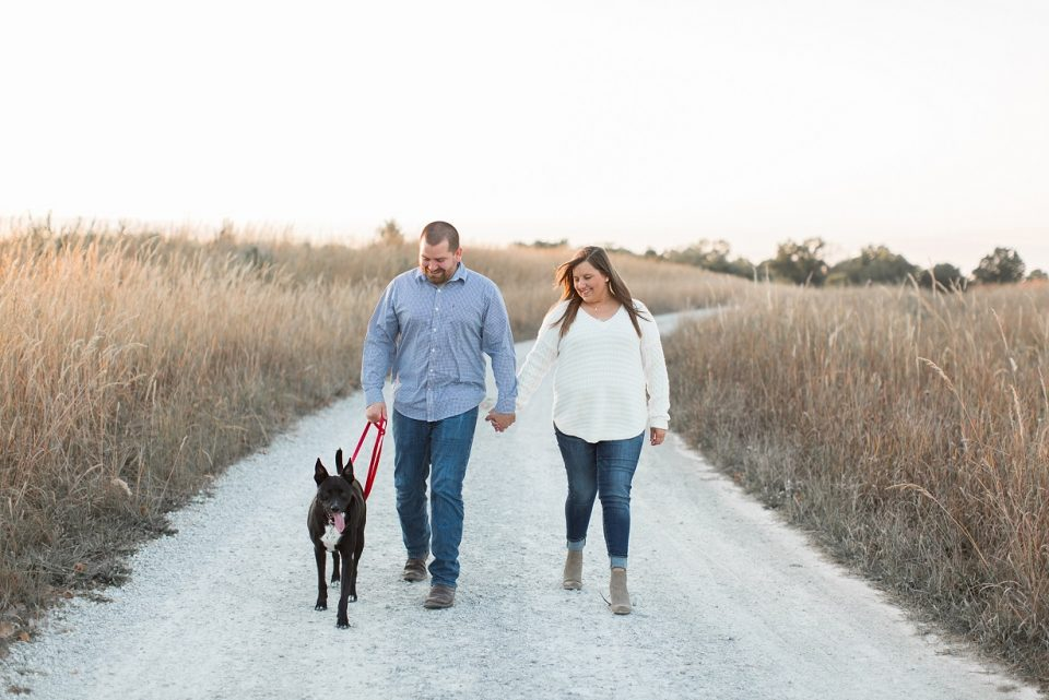 happy couple walking with dog on dirt road