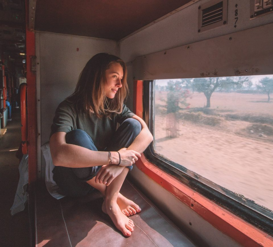 woman sitting in moving bus looking out the window