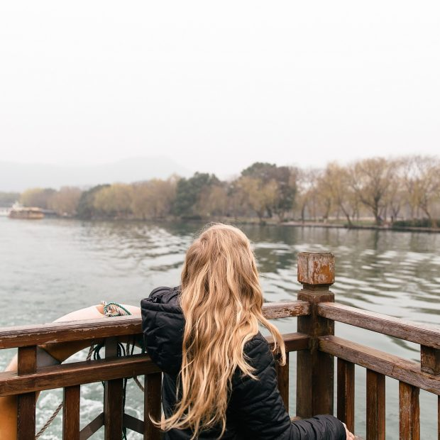 girl looking out over lake on a cloudy day
