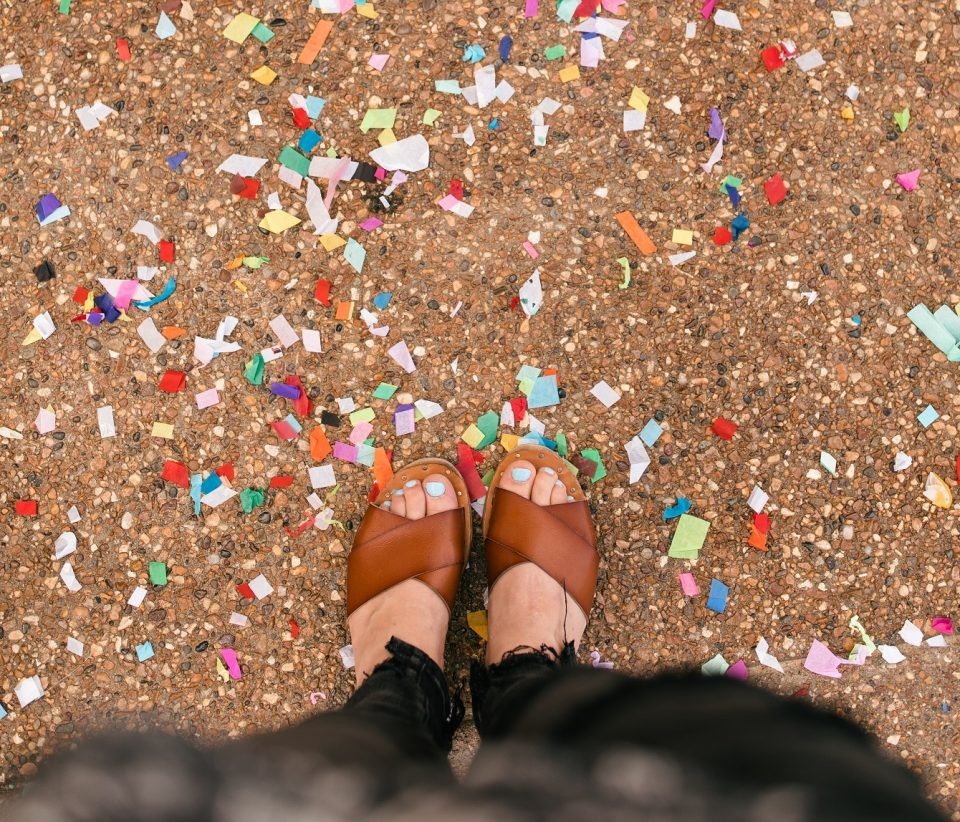 feet surrounded by confetti on the ground