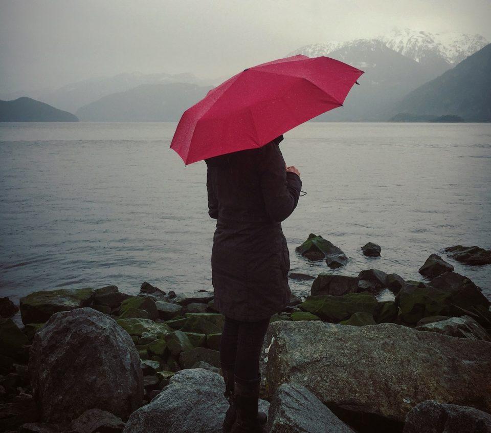 person holding umbrella on rainy day
