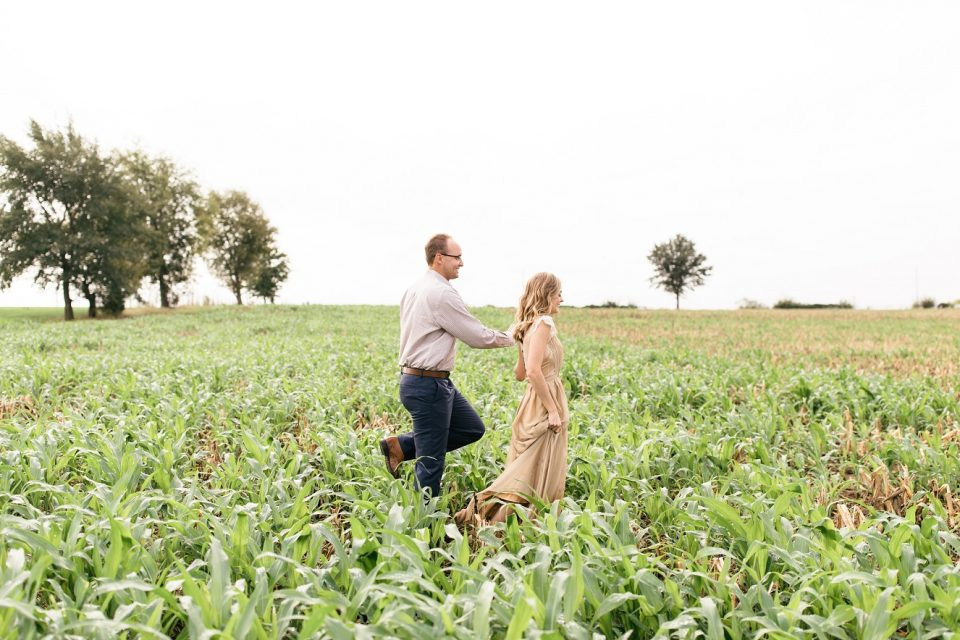 happy couple running through fields