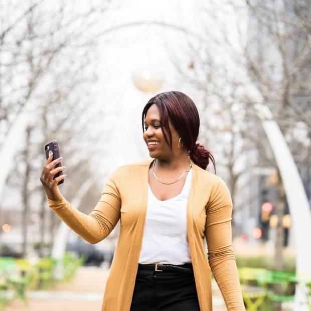 happy woman looking at her phone taking a selfie